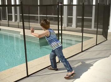 boy pushing pool fence