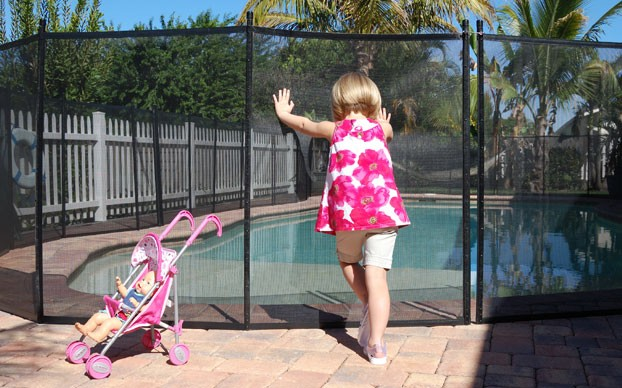 Girl Pushing on Pool Fence