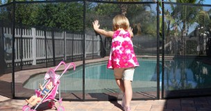 Girl Pushing on Pool Fence